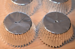 Simple baking cups are pierced with a two holes then an ornament hanger is threaded through. Pinch the wire to keep it in place.