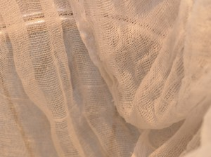 Boiled cheesecloth is doubled and draped inside a sieve.
