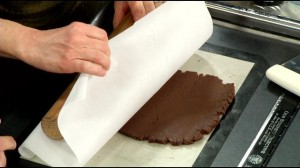 Removing the top parchment paper after rolling out.